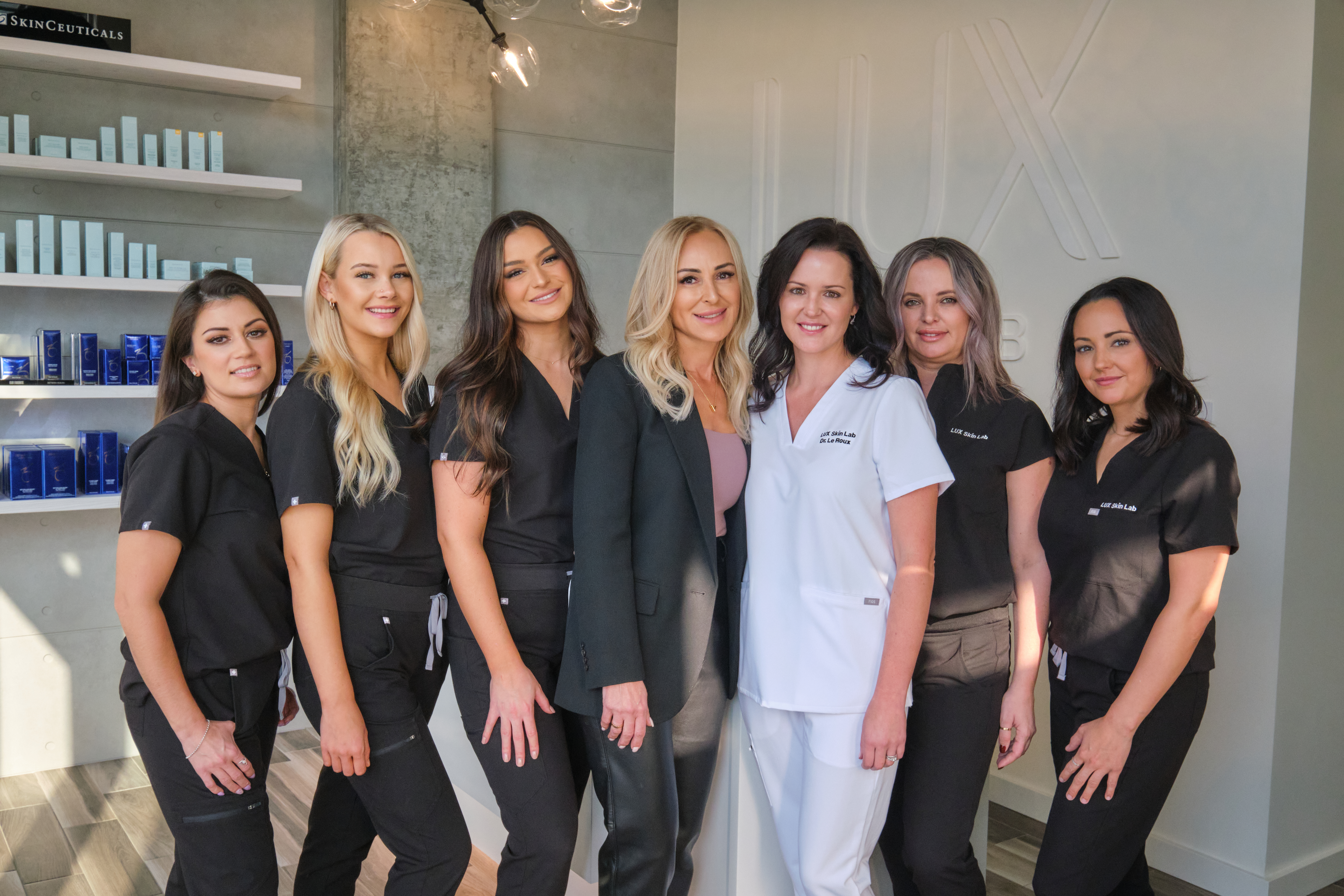 A team of skincare specialists pose for a group picture in their clinic. The seven women are all smiling.
