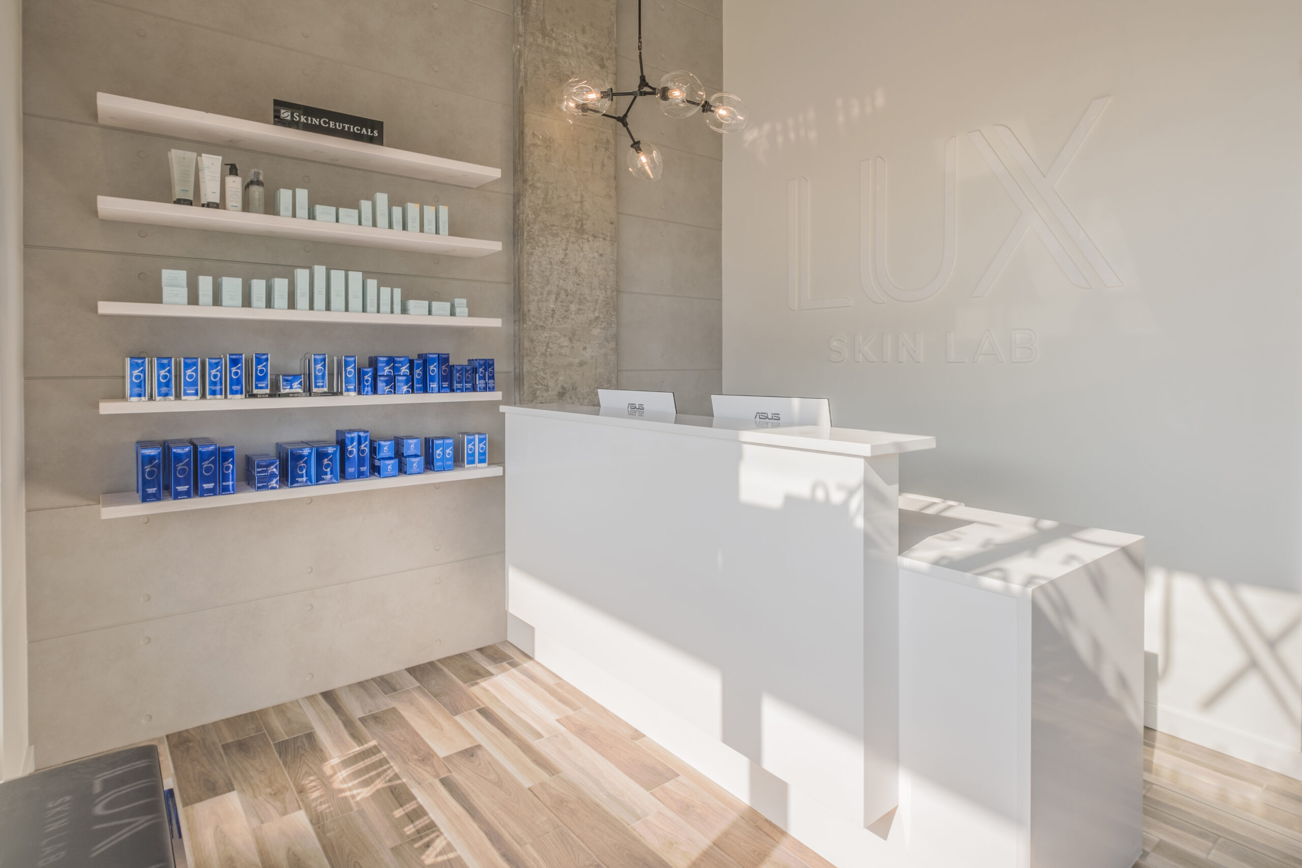 Interior of the LUX Skin Lab clinic featuring a white desk and a wall shelf filled with products.